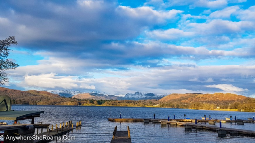 A photo taken during golden hour of Windemere Lake, with a few piers over the water in the front, and snowy mountains in the back. The sky is blue, with clouds here and there.
