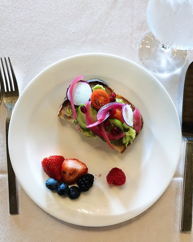 avocado toast with fresh tomatoes and pickled onions for breakfast