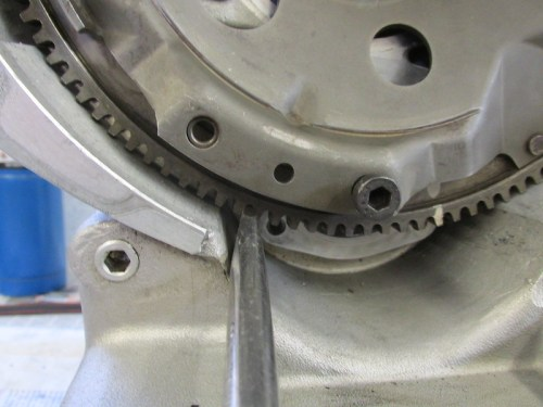 Use Large Flat Blade Screwdriver Between Flywheel Teeth to Stop Flywheel From Turning