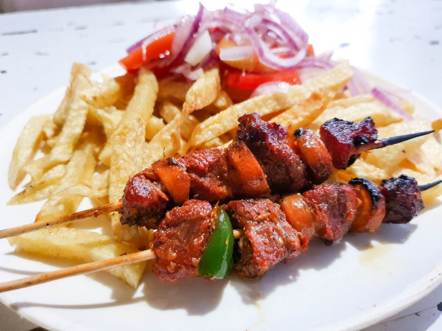 Two skewers with beef, green peppers and carrots which have just been taken of the grill, next to a portion of golden french fries and a tomato and onions salad.