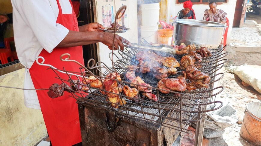 A man wearing a red apron turning around the skewers with meat, on the grill