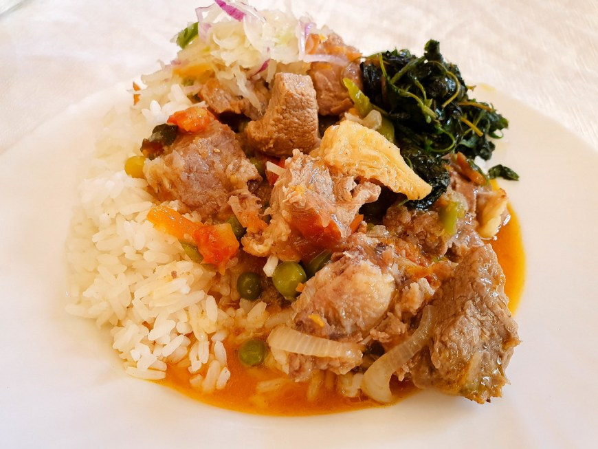 A plate with white rice, beef stew with onions, carrots and peas, and a green steamed salad