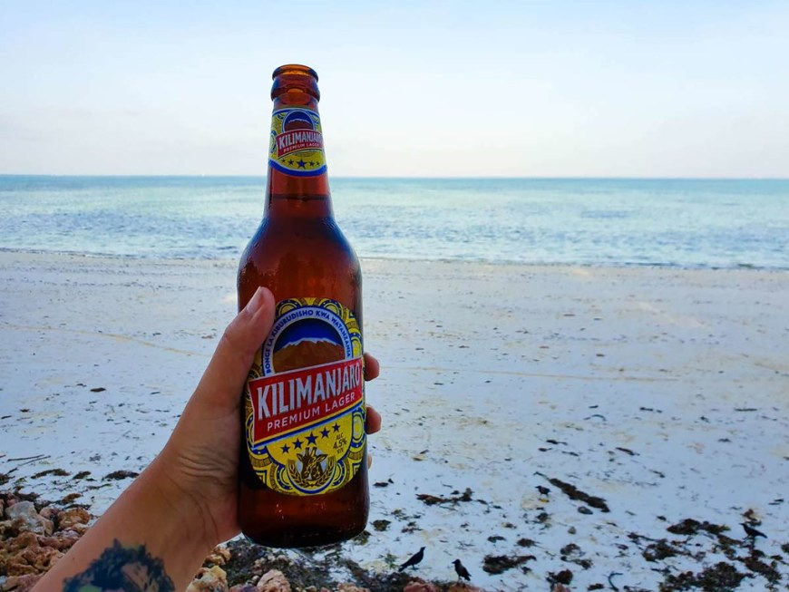 My hand holding a bottle of Kilimanjaro beer on the beach, at sunset. Sand and the sea are in the background