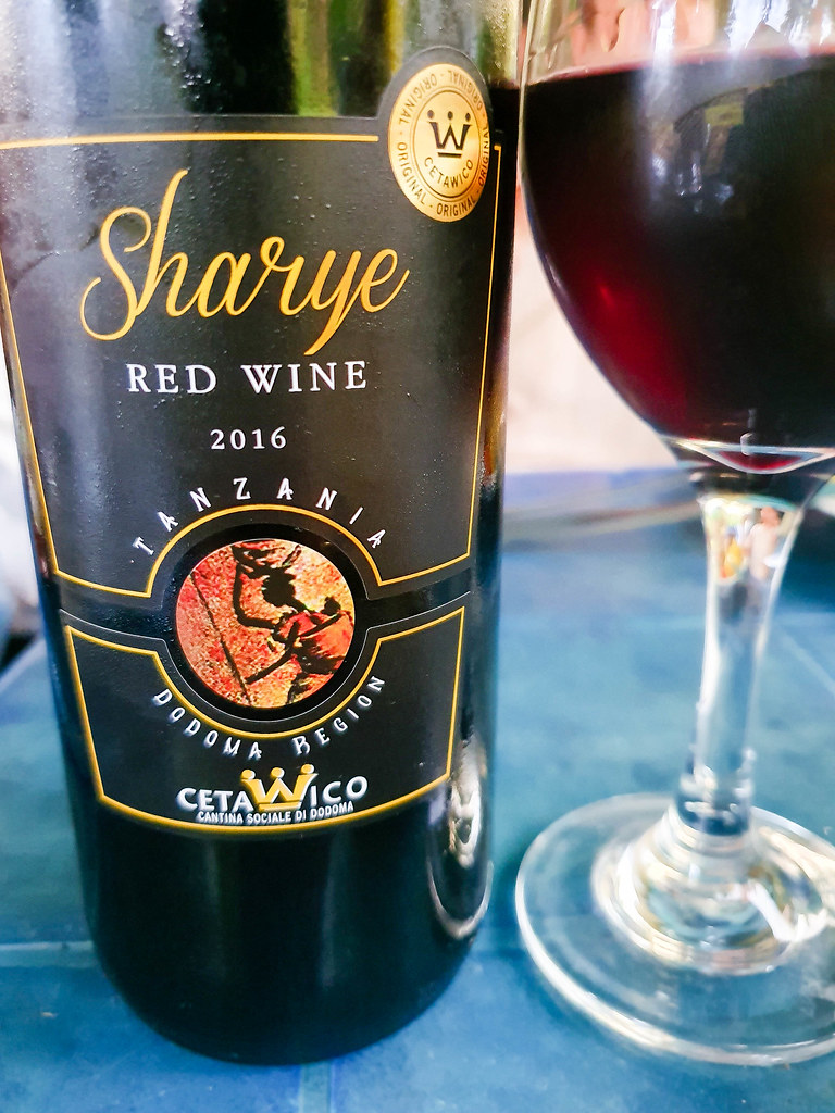 A close-up of a bottle of Sharye red wine, which has a black label with golden writing of the name on it. Next to it there is a glass filled with the dark red colored wine.