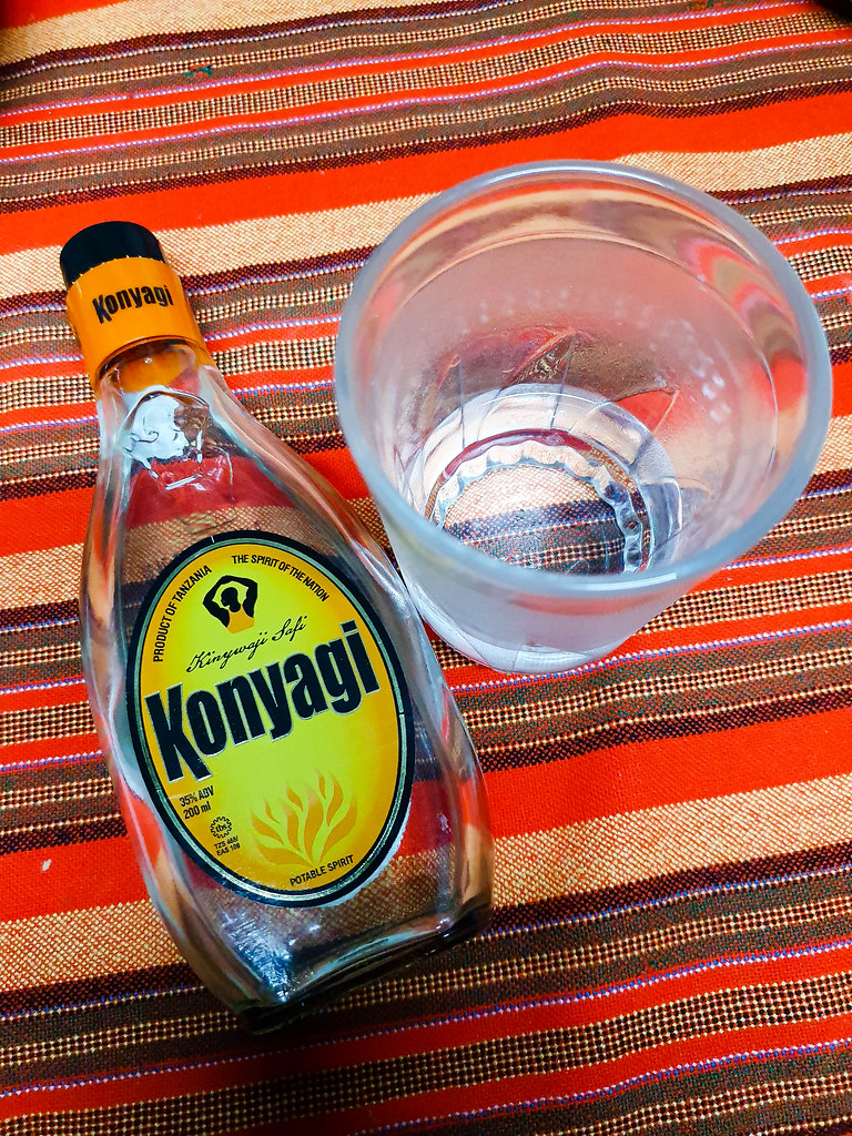 A bottle of Konyagi lying flat on a red stripes table cloth. The label of the drink is yellow. Next to the bottle there is an empty glass.