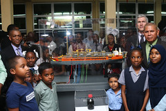 Director of Energy, Dr. Mark Bynoe, Minister of Social Cohesion, Dr. George Norton, ExxonMobil Country Manager, Rod Henson along with children of Guyana's soil at the scale model of the Liza Destiny.