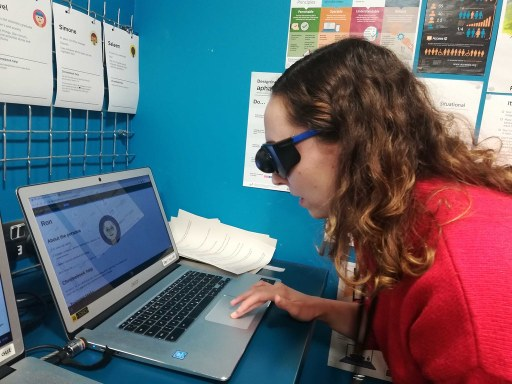 blind female student listening to screen reader describe information on his computer screen