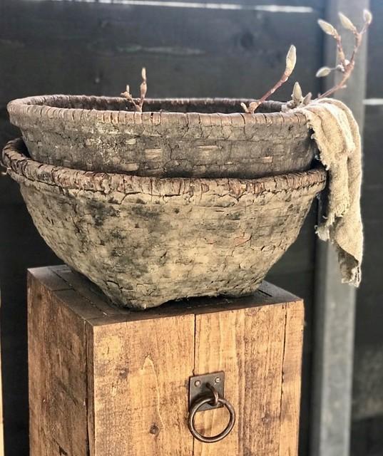 Rijstmanden op houten zuil met ring en linnendoek