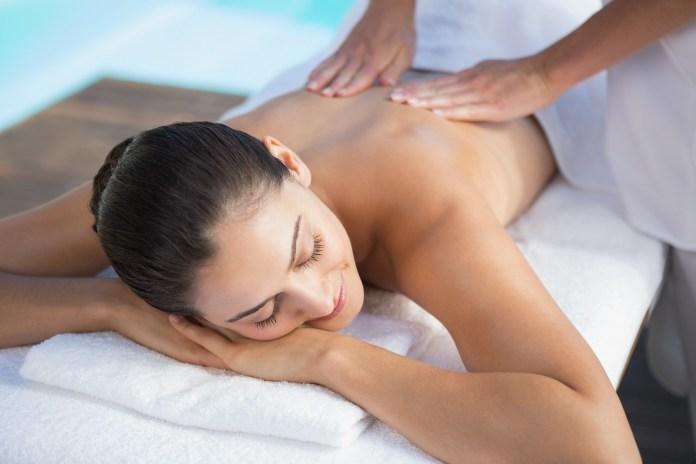Smiling brunette enjoying a massage poolside
