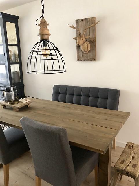 Draadmand lamp boven landelijke eettafel met kolompoot