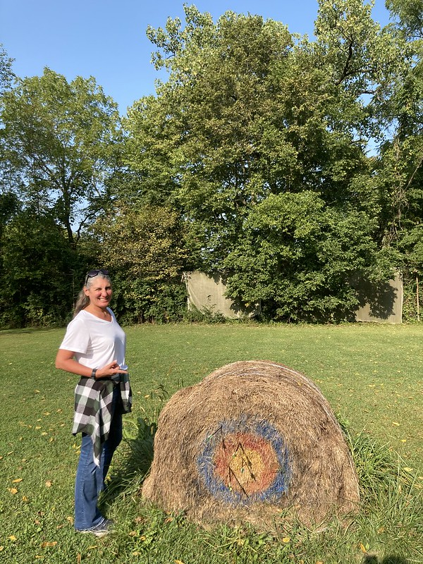 Krissy Scalzi pointing to the archery target she was shooting. She has gotten a bullseye.