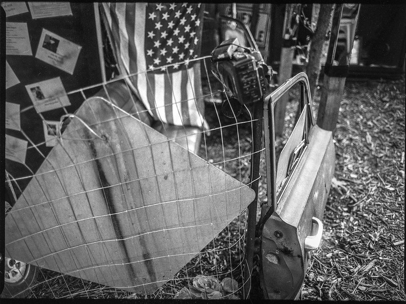 installation, wire fence, street sign, car door, flag, Burton Street Peace Garden, Asheville, NC, Mamiya 645 Pro, mamiya sekor 45mm f-2.8, Fomapan 200, HC-110 developer, 9.19.20