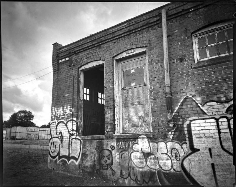 graffitied facade, missing door, abandoned mill, brick, Asheville, NC, Graflex Crown Graphic, Graflex Optar 90mm f-6.8, Bergger Pancro 400, HC-110 developer, 11.8.20
