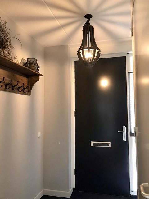 Zwarte voordeur landelijke hal kapstok krans