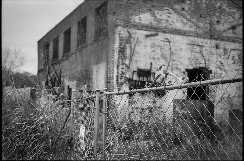 urban decay, abandoned brick mill, metal fence, tall wild grasses, river district, Asheville, NC, Minolta XG-M, Super Albinon 28mm f-2.8, Ilford FP4+, Moersch Eco film developer, 12.17.20