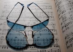 Blue sun glasses refraction music book