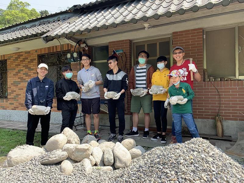學生搬運石頭堆防坡堤