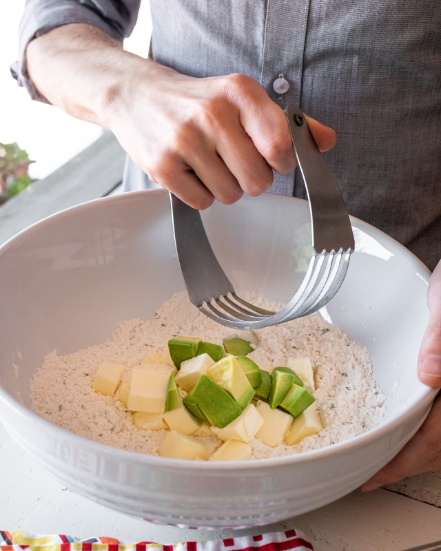 cutting the butter and avocado cubes into the pastry dough