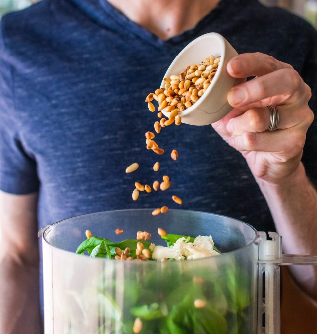 adding toasted pine nuts to the food processor