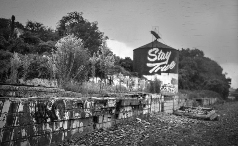 """abandoned and overturned couch II, """"Stay True"""" storage silo, graffitied wall, trackside, railroad district,  Asheville, NC, Goerz Pocket Roll Film Tenax camera, Fomapan 200, HC-110 developer, 8.12.21"""