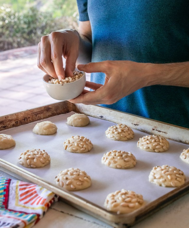 topping the mounds of dough with pine nuts