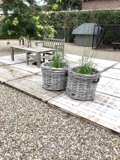 Terras van steenschotten met grind rieten manden met planten