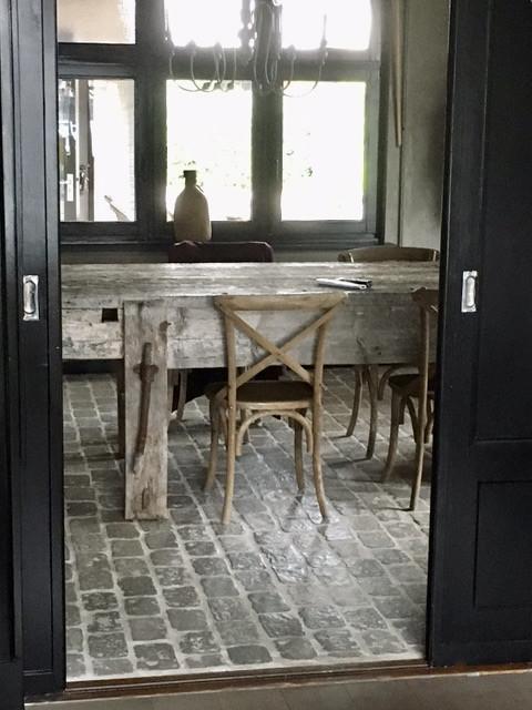 Lange houten tafel met houten stoelen RAW Stones vloer eetkamer