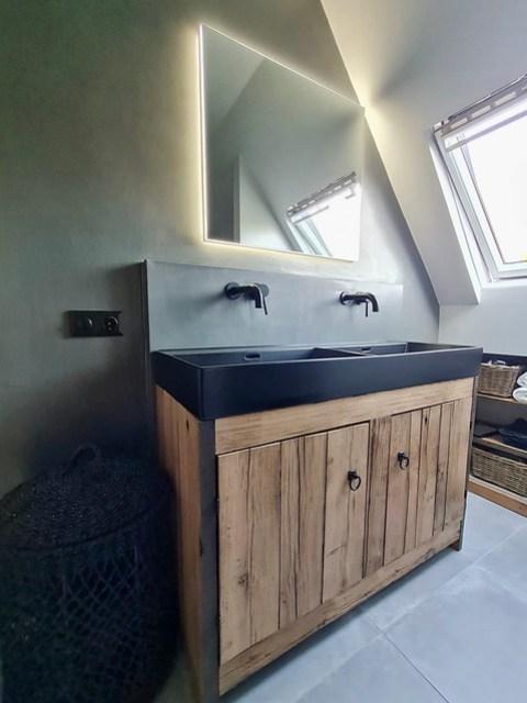 Rechthoekige spiegel met licht erachter boven houten badmeubel zwarte inbouw kranen