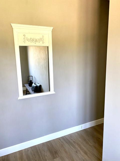 Kalkverf muur landelijke spiegel houten bankje zwarte kussens