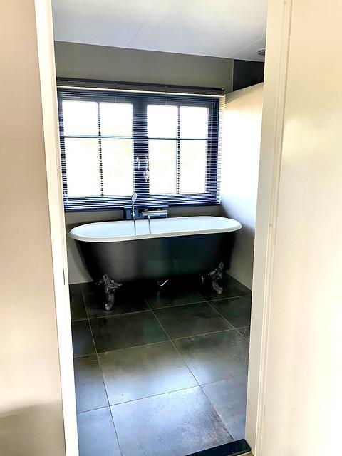 Bad op pootjes voor het raam met zwarte kozijnen in landelijke badkamer
