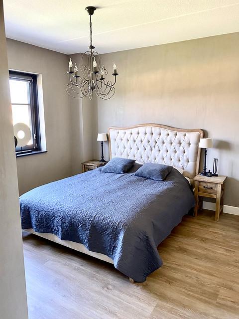 Gecapitonneerd hoofdbord kroonluchter landelijke slaapkamer