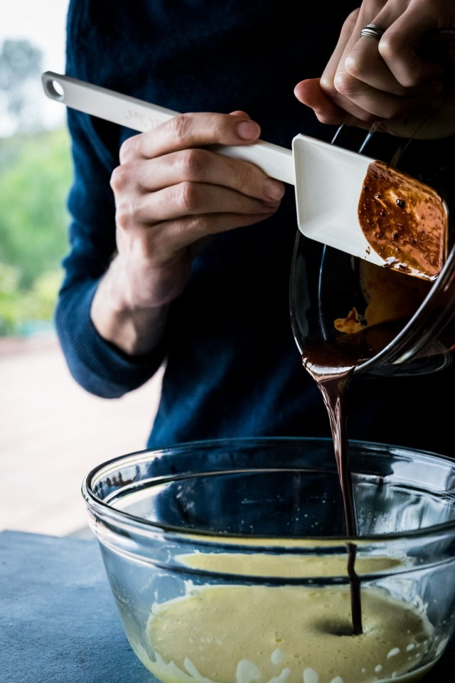 adding melted chocolate to the whipped eggs