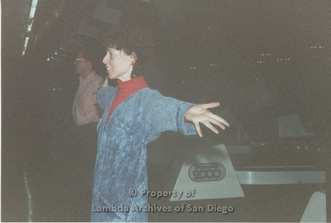 P001.134m.r.t Bowling 1991: Woman in a jean jumpsuit with her arms stretched out