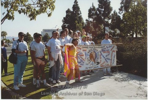 "P001.024m.r AIDS Walk 1990: William A. Jellison as ""Safer Sex Dude"" with group of men and Project Life Gaurd banner"