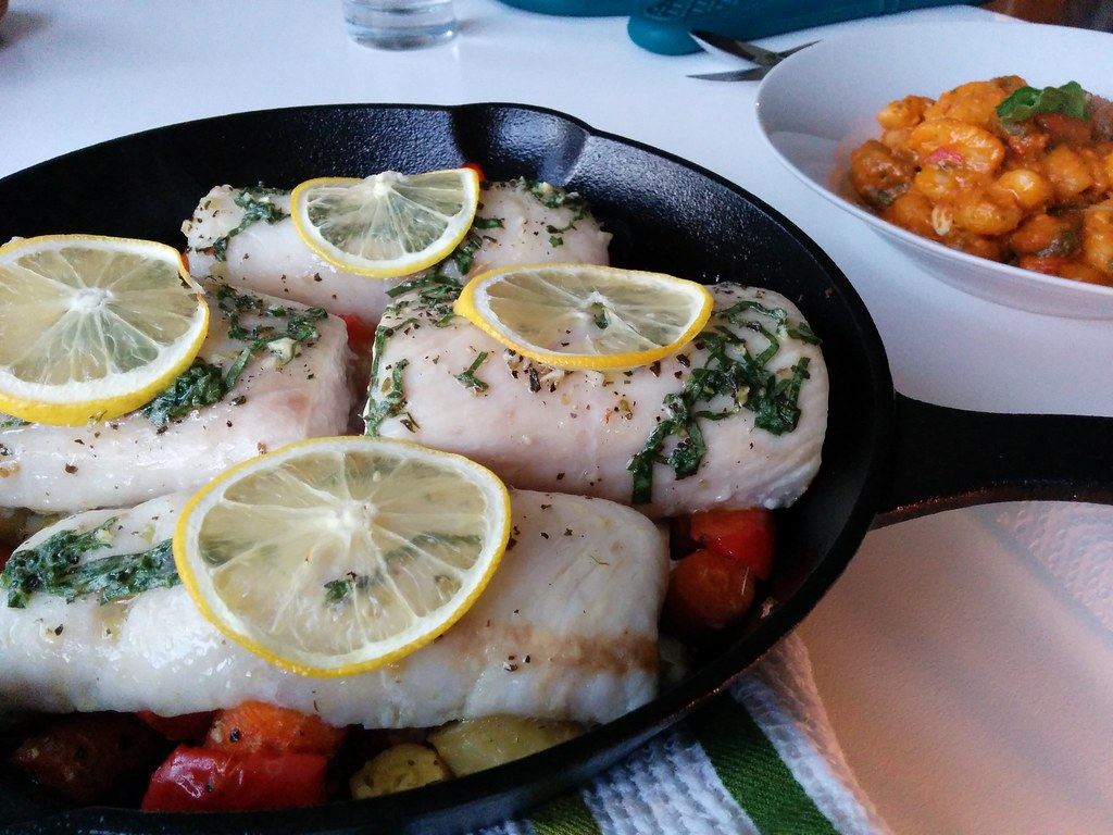 Delicious fish in a cast iron pan with slices of lemon and herbs
