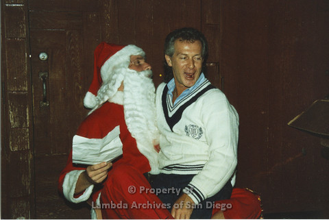 P001.287m.r.t X-mas: man in white sweater sitting on Santa's lap, Santa is holding a sheet of paper
