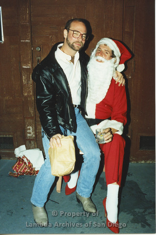 P001.286m.r.t X-mas: man in leather jacket holding a present sittinng on Santa's lap