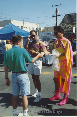 P001.101m.r.t City Fest 1991: 3 men, one wearing a yellow and pink costume