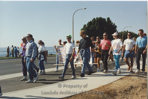 P001.116m.r.t AIDS Walk 1991: People walking behind and in front of a banner (Project Life Guard)