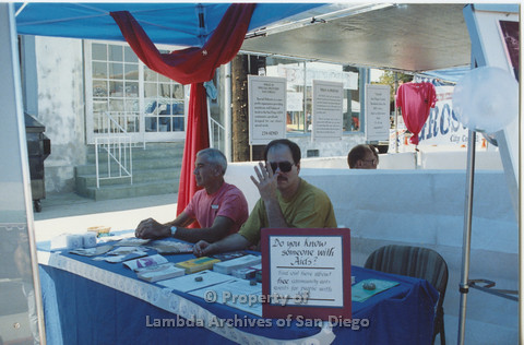 "P001.097m.r.t City Fest 1991: Dr. Bill Crawford (left) and another man in a booth, sign ""Do you know someone with Aids?"""