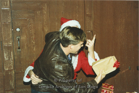 P001.279m.r.t X-mas: man in brown leather jacket sitting on Santa's lap holding a present
