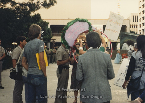 P024.101m.r.t Myth California Protest, San Diego, June 1986: Sign attached to hoola-hoop (Beauty Obediance School)