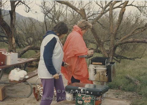 P024.057m.r.t Cathy Moore's 34th Birthday, Halley's Comet Weekend, Anza Borrego Desert 1986: 2 women working with a BBQ in the rain.