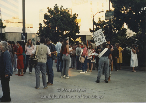 P024.123m.r.t Myth California Protest, San Diego, June 1986: shot of crowd, person holding a sign (Judge Not Lest Ye Be Judged Also)