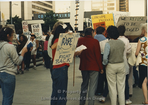 P024.113m.r.t Myth California Protest, San Diego, June 1986: people holding signs, person in the middle's sign  (Wimmin Fight Back)