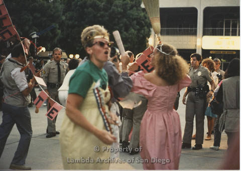 P024.132m.r.t Myth California Protest, San Diego, June 1986: lady in a pink dress holding a broom with a sign (Welcome to the Meat Market