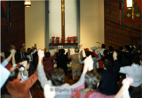 P103.044m.r.t Dignity San Diego: Men and women holding raised and clasped hands up in the air