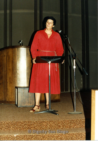 P103.207m.r.t Digntity San Diego: Woman in red dress standing in front of small podium