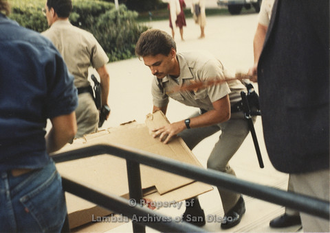 P024.093m.r.t Myth California Protest, San Diego, June 1986: police officer picking up cardboard