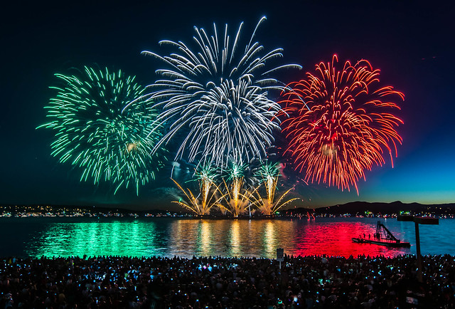 Green, blue, and red fireworks burst over a river at night